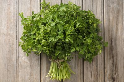 Large bunch of Italian parsley tied with twine and sitting on a wooden background