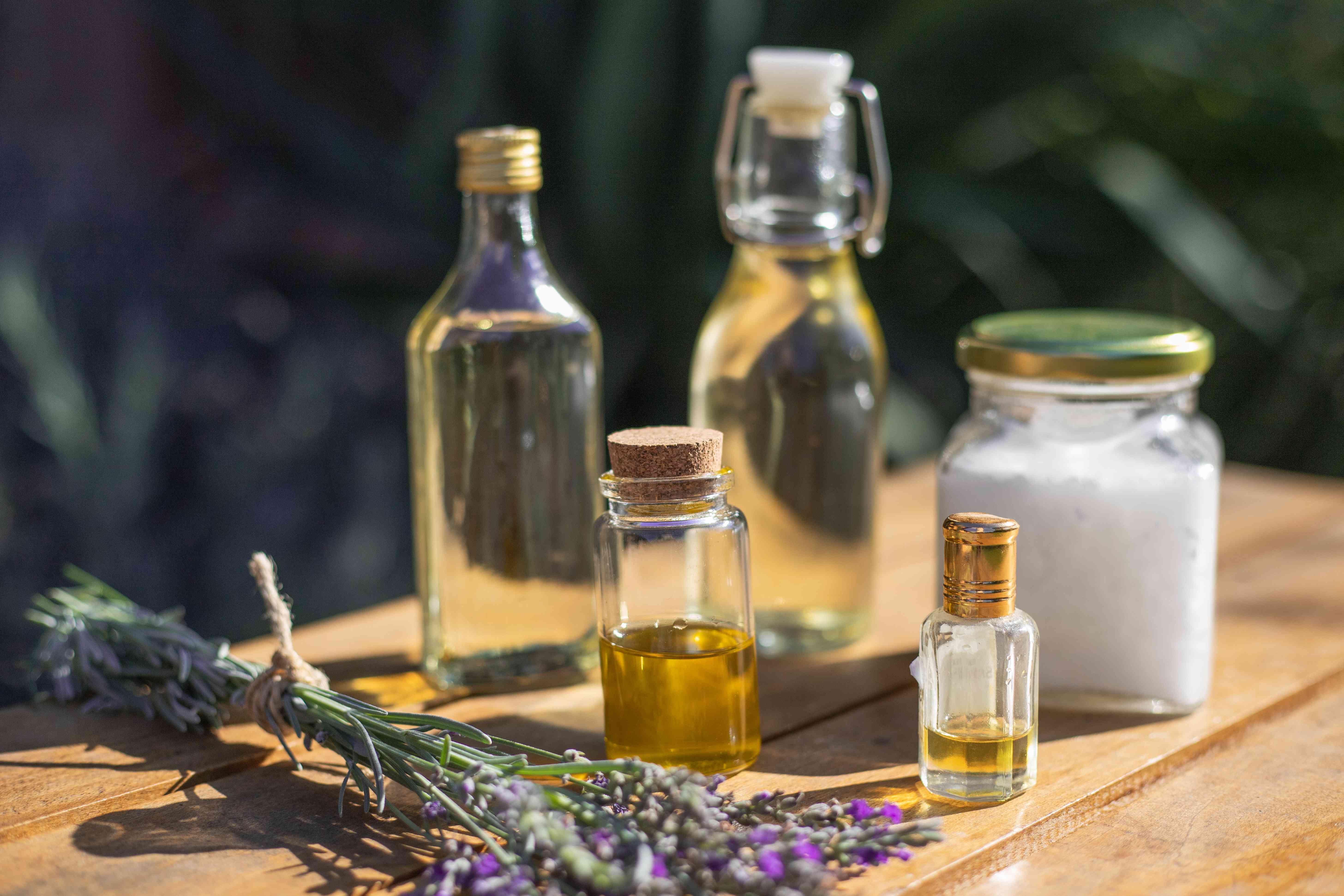 ingredients for DIY lavender oil on wooden table include dried lavender, carrier oil, essential oil