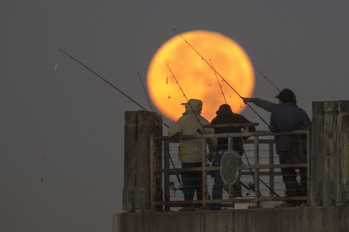 The moon sets behind people fishing on a pier during its closest orbit to the Earth since 1948 on November 14, 2016 in Redondo Beach, California.