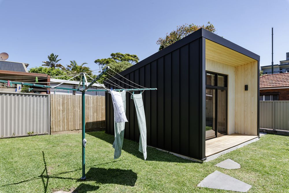Exterior of tiny home tucked in the corner of a backyard