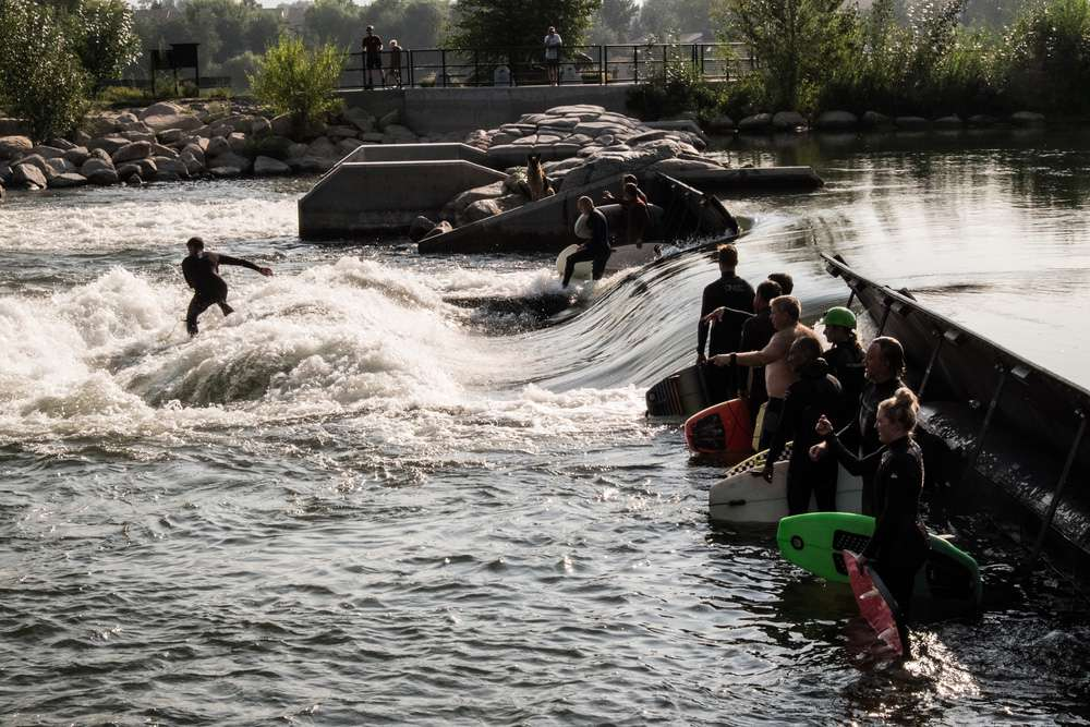 One surfer riding a wave while other surfers stand with their boards at Boise whitewater park