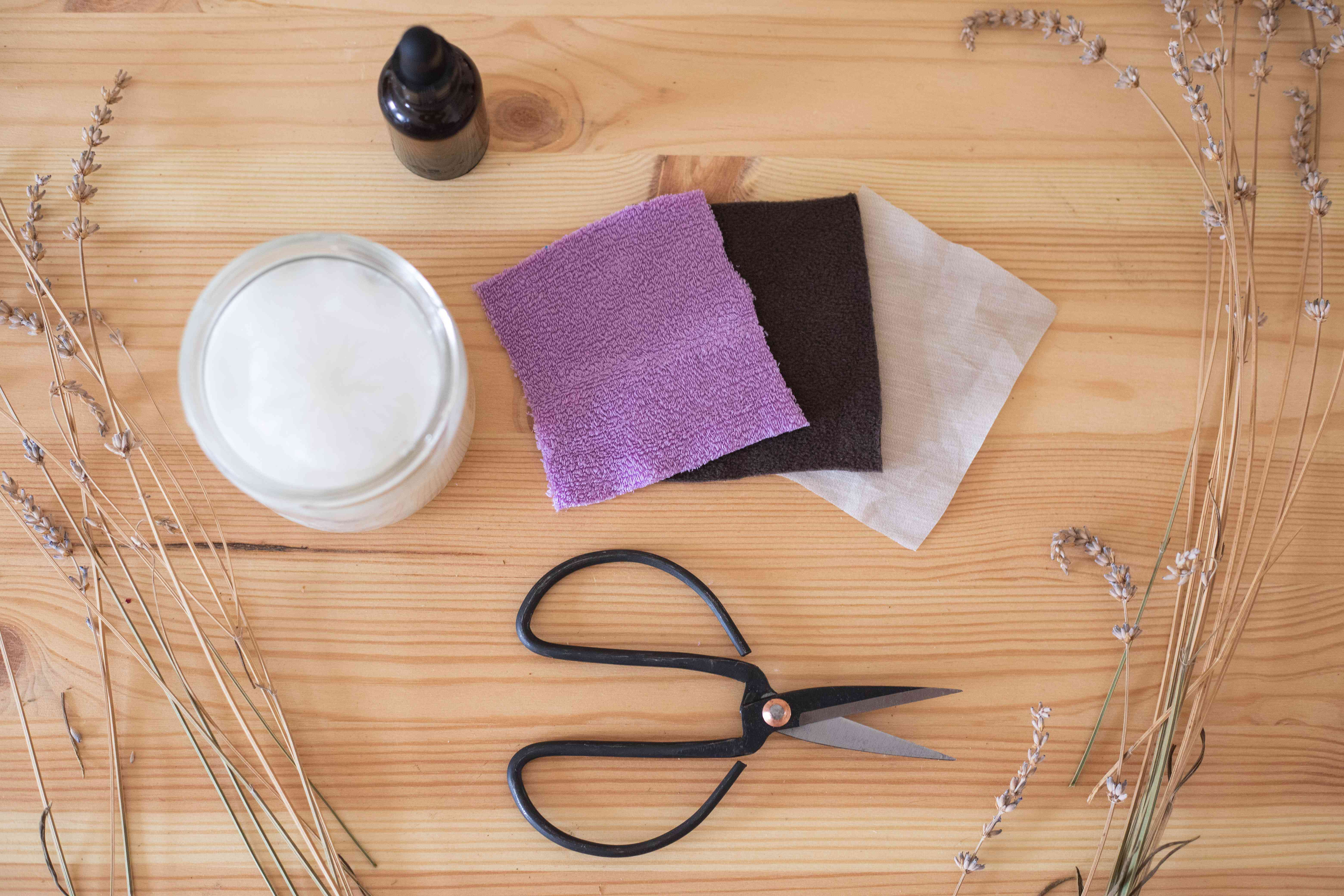 flat lay of zero waste beauty with felt cloth makeup removers, scissors, and coconut oil