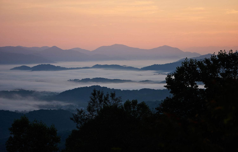 The morning sun rises above the dense fog enveloping the Blue Ridge Mountains