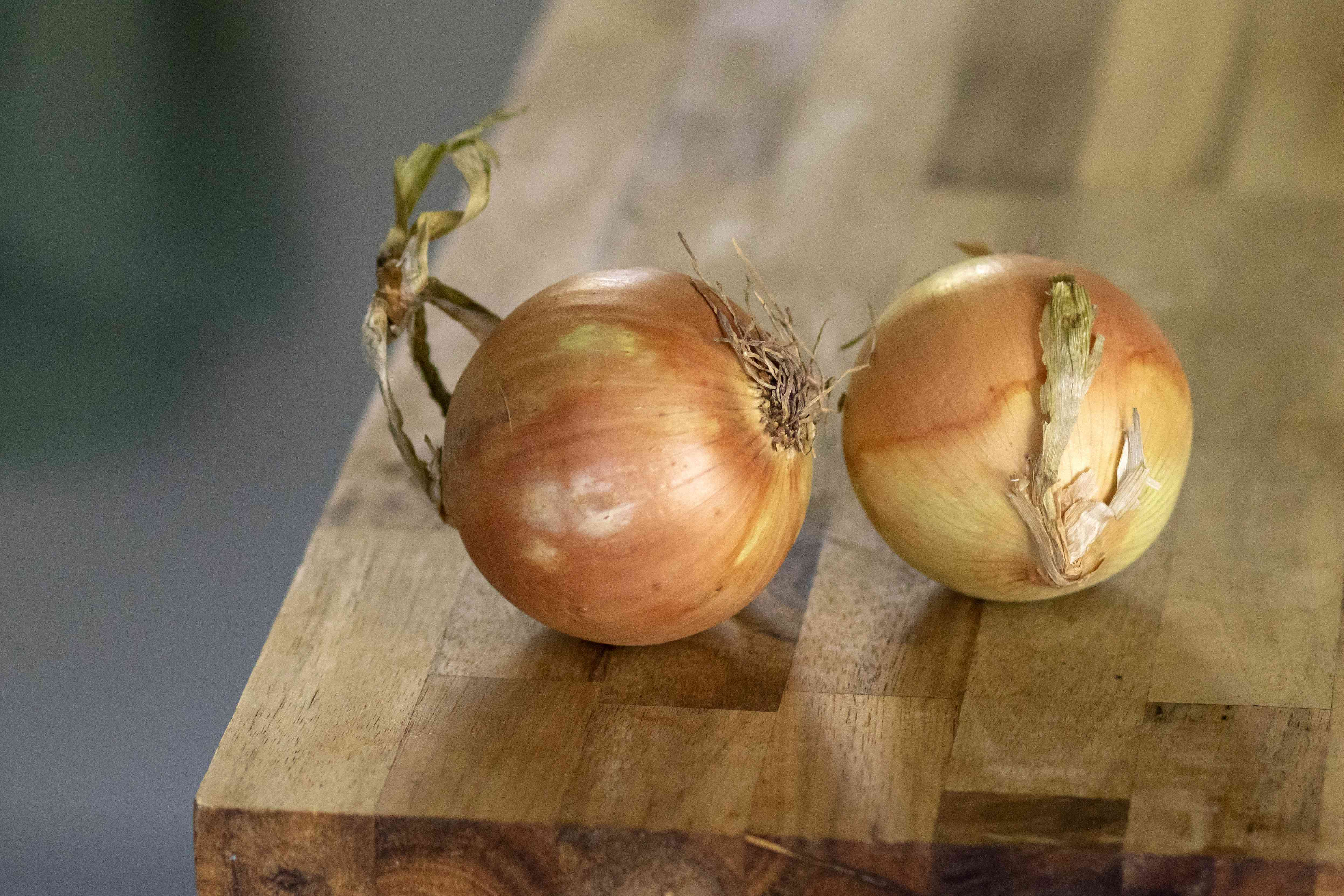 two onions on wooden table