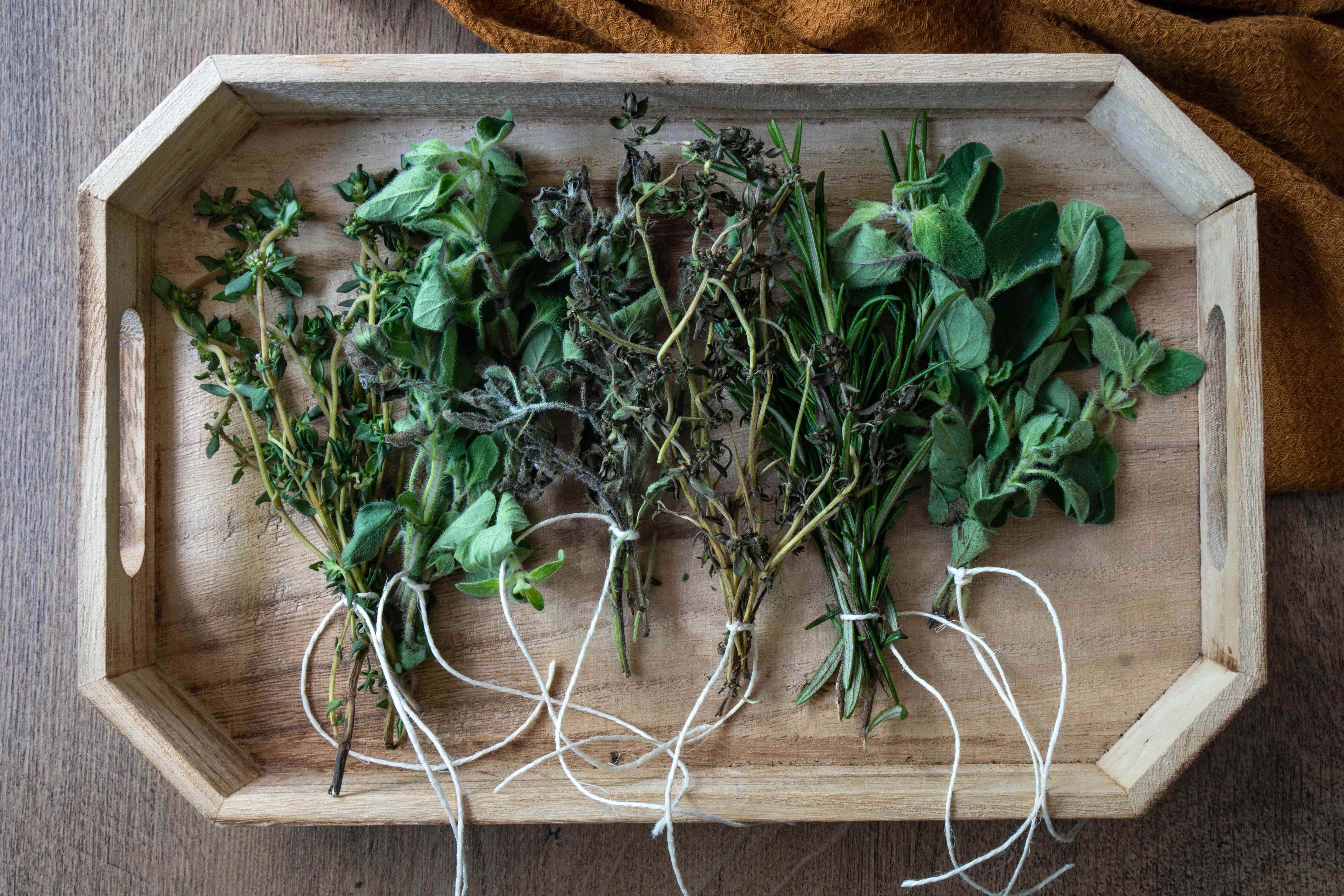 various dried herbs tied with white twine on blonde wooden tray
