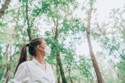 Woman hiking in forest nature wearing face mask