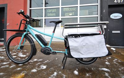 A blue cargo bike with a rack and storage outside of a bike shop.