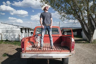 man stands in back of truck