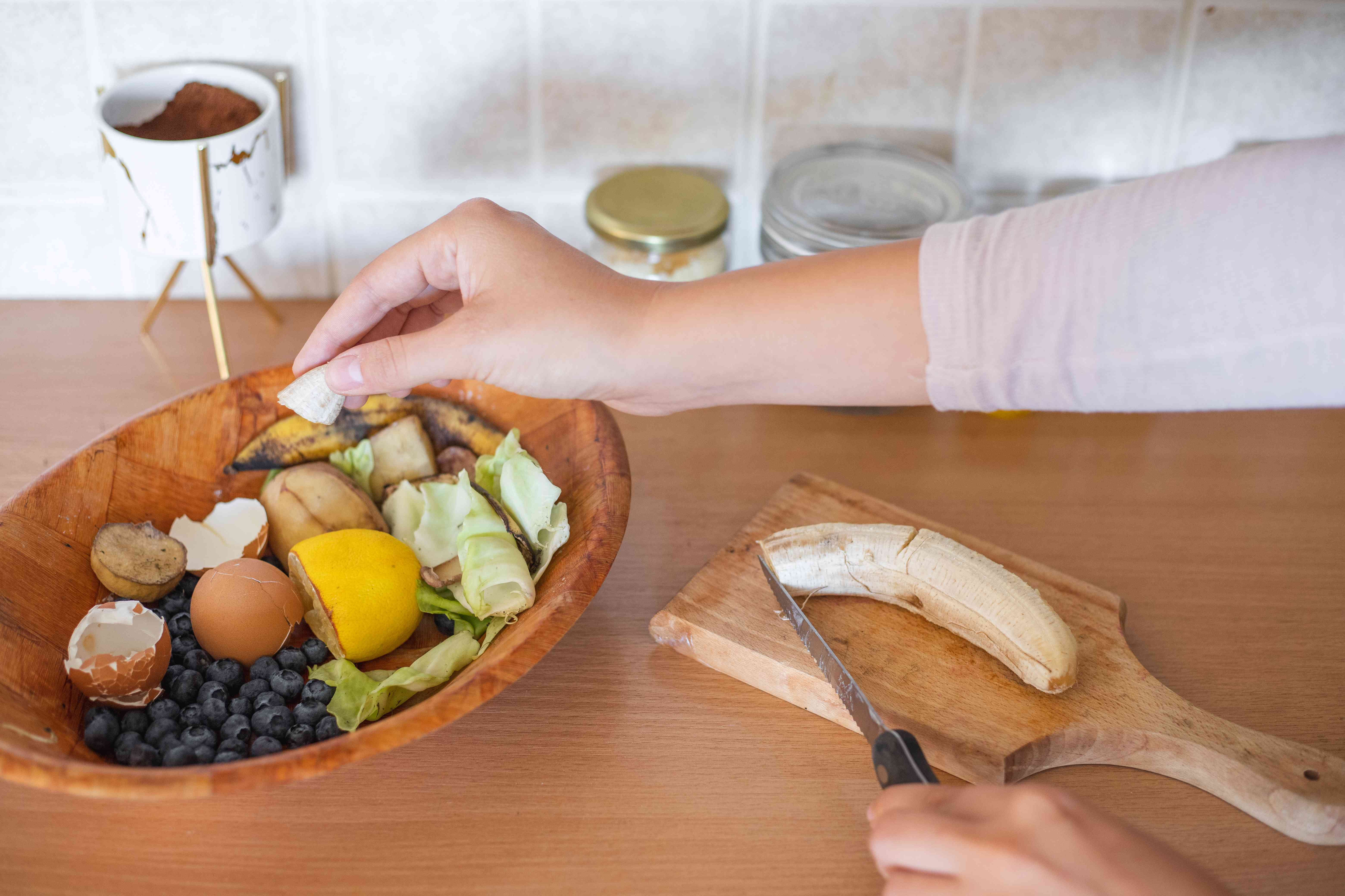 person in kitchen puts old food scraps and egg shells into bowl for composting later
