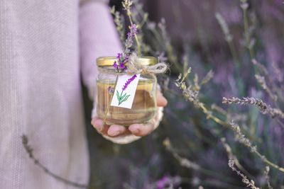 woman in sweater holds DIY lavender essential oil in glass jar