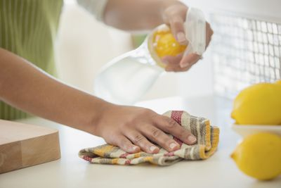 Woman using spray cleaner on counter top