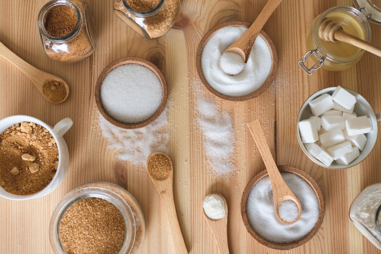 multiple varieties of sugars and sugar substitutes in wooden and ceramic jars bowls
