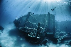 A small shipwreck with a snorkeler diving down from the surface.