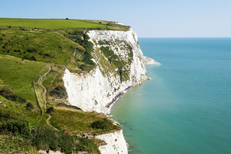 The Chalky White Cliffs of Dover rise above the greenish-blue waters below