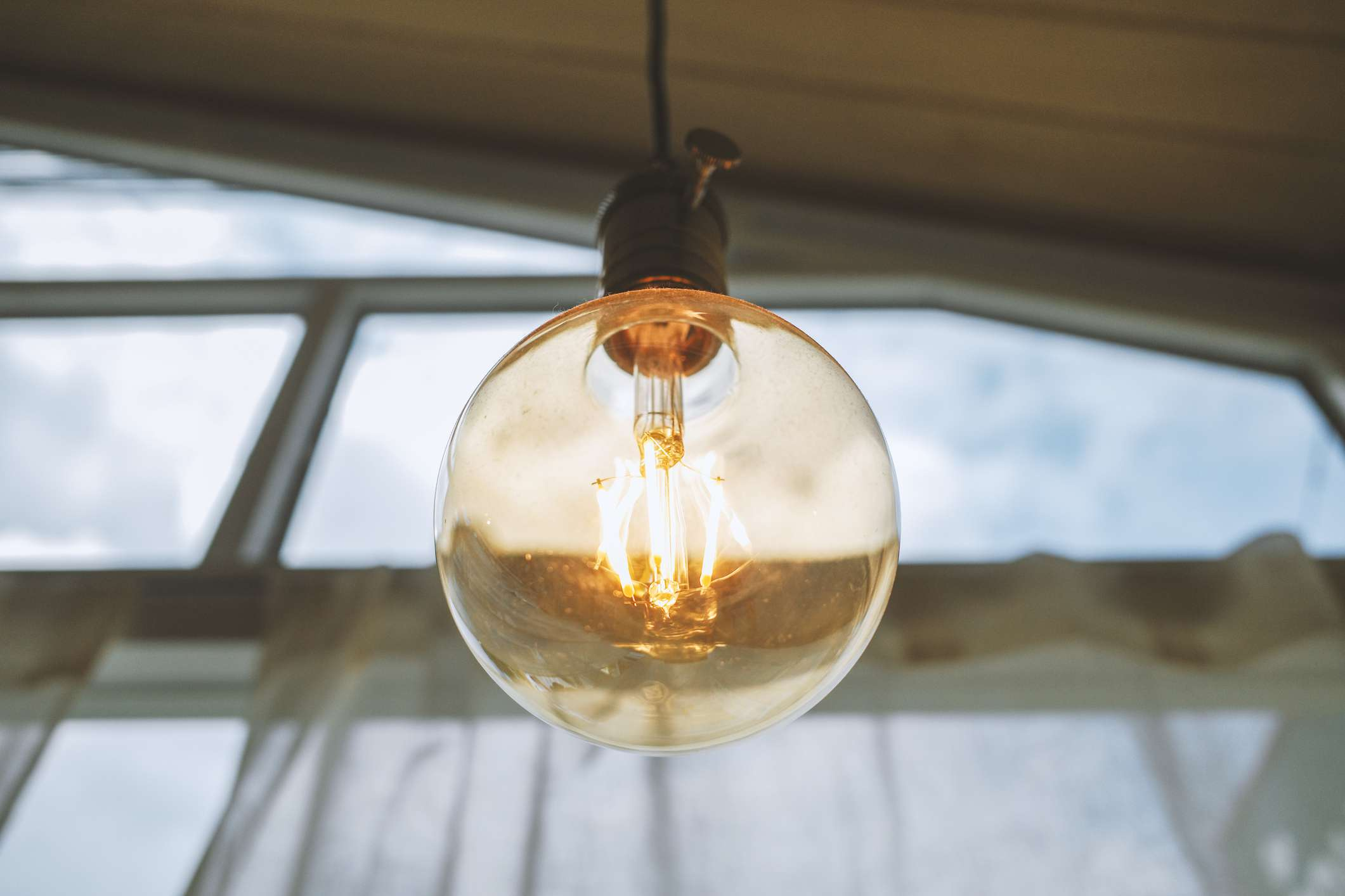 An incandescent light hangs from the ceiling by a window.