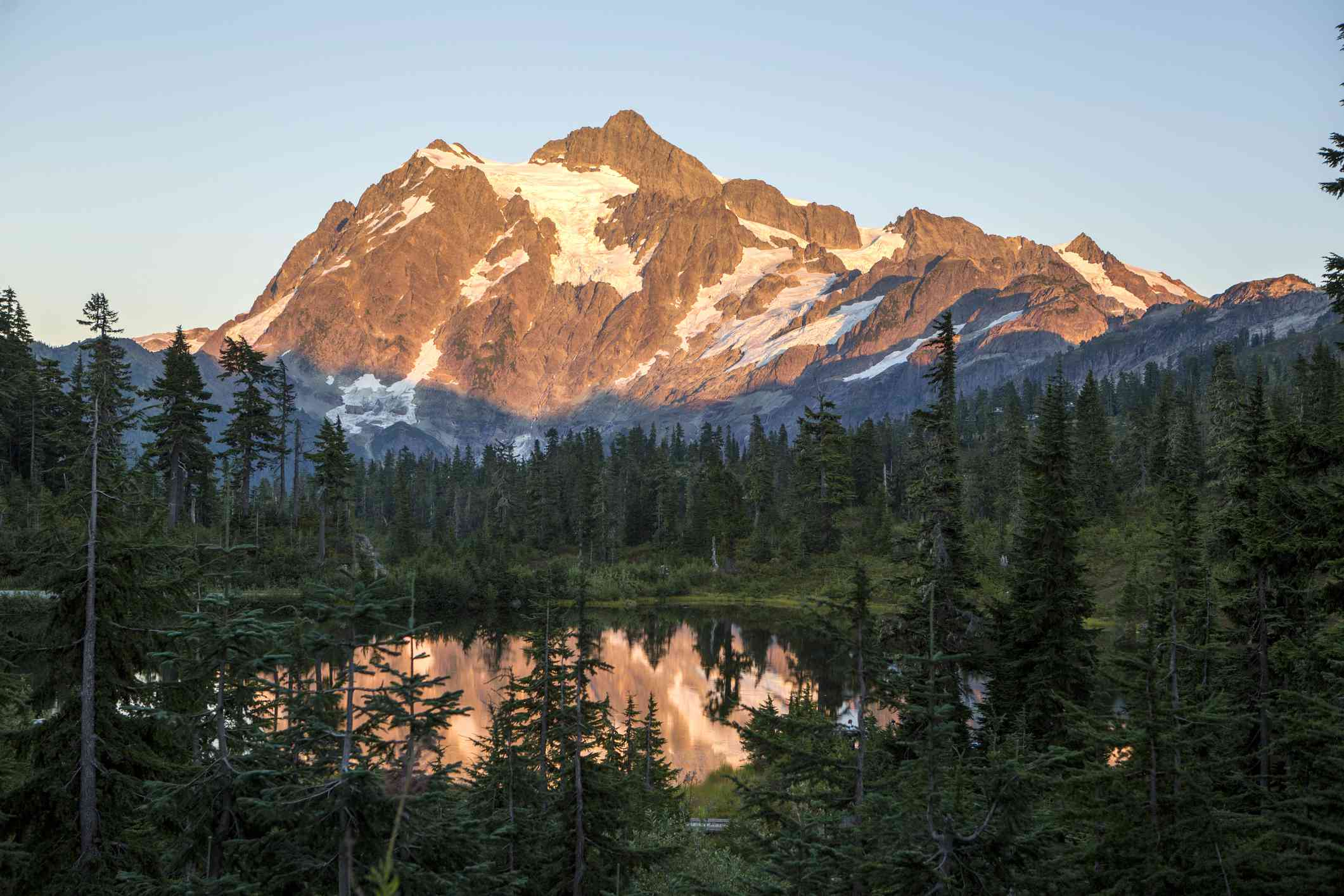 View of Mount Baker at dawn across a mountain lake