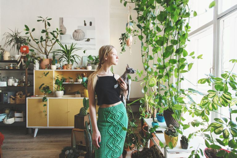 A young white woman in an apartment with cat surrounded by plants.