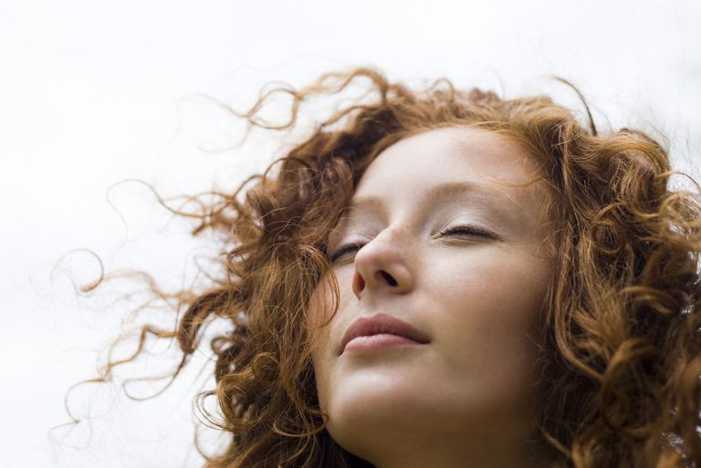 A redhead woman with curly windblown hair.