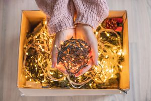 woman in pink sweater holds out bundle of glowing Christmas lights above full cardboard box