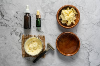 flat lay of ingredients for diy shaving cream including shea butter and oil