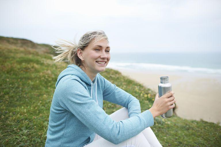 Woman in sportswear sitting on Atlantic coastline with an aluminum water bottle