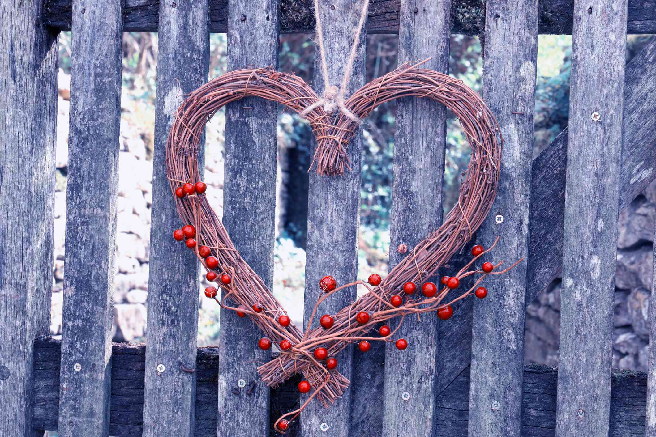 Heart Shape Made From Dried Plant Stems Hanging On Wooden Fence