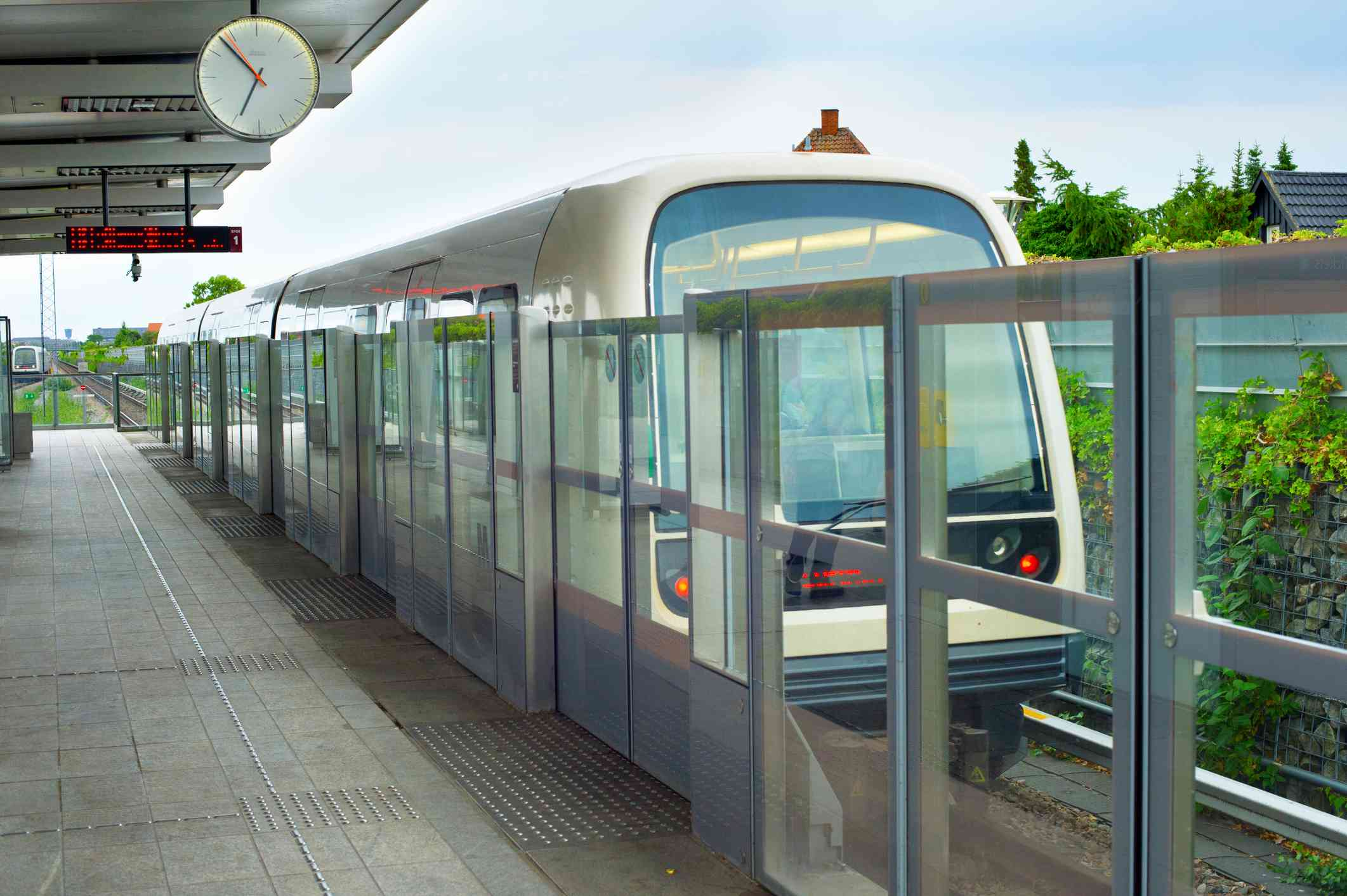 subway train at an outdoor station in Copenhagen next to a clean platform walkway with clear glass gates and a clock under an overhang