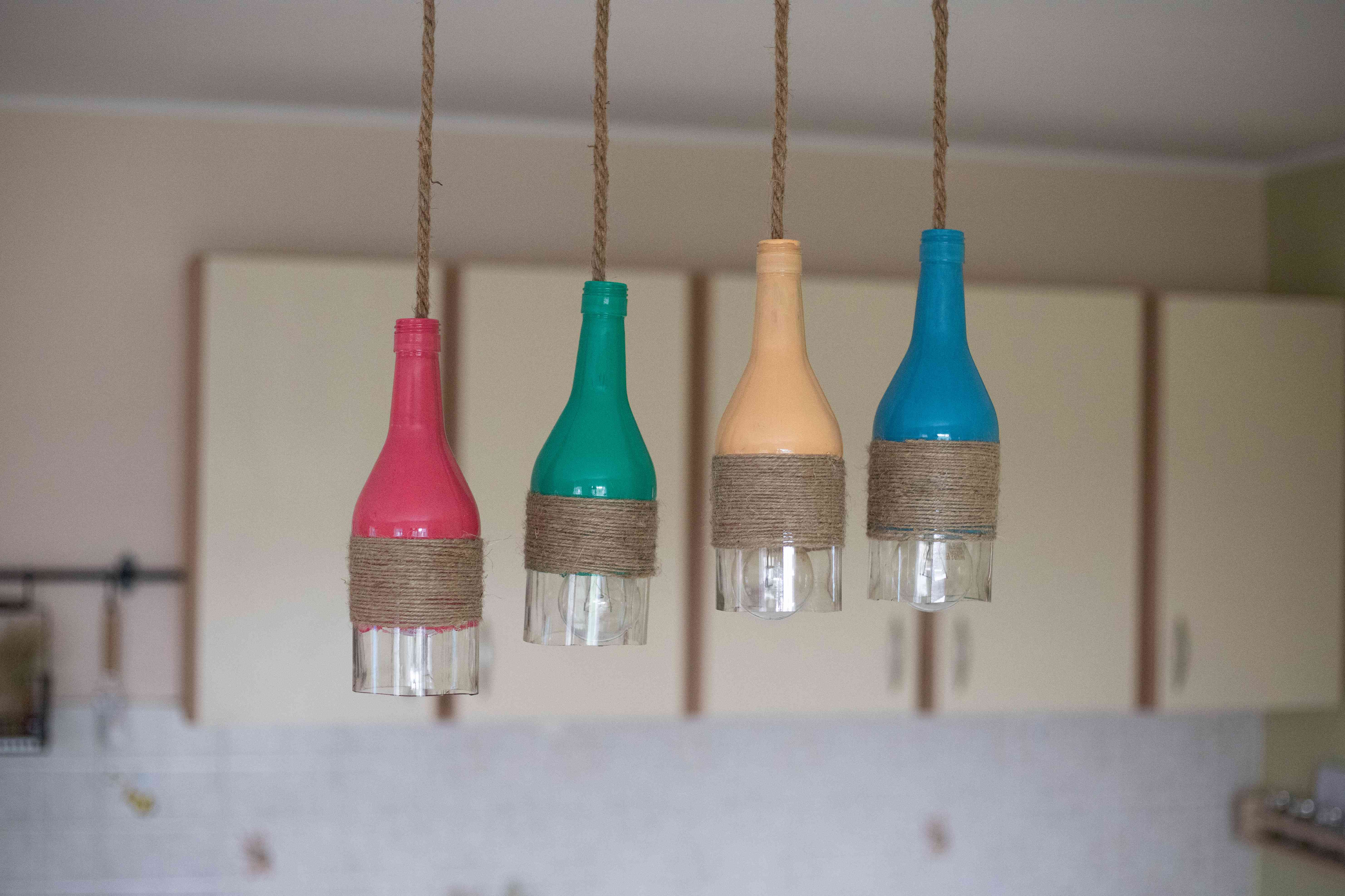 wine bottles upcycled and painted and hung with twine as lighting pendant