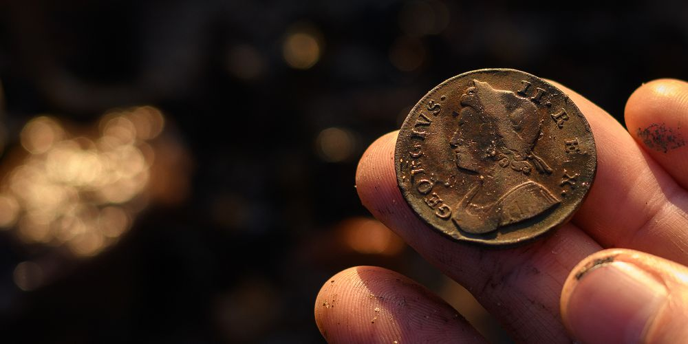 Hand holding a Roman coin.