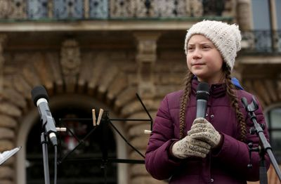 Greta Thunberg holds a microphone during a Fridays for Future protest in Hamburg