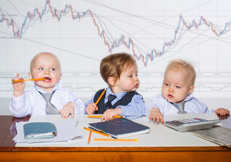 three young kids in neckties and button down shirts sitting at a desk in front of a large graph