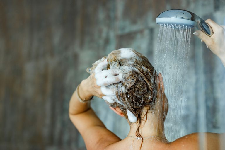 A woman lathering up shampoo in her hair and holding the shower head.