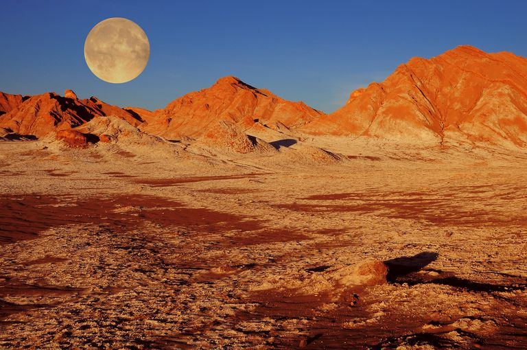 Full moon at sunset above glowing red mountains in the Atacama Desert, Chile.