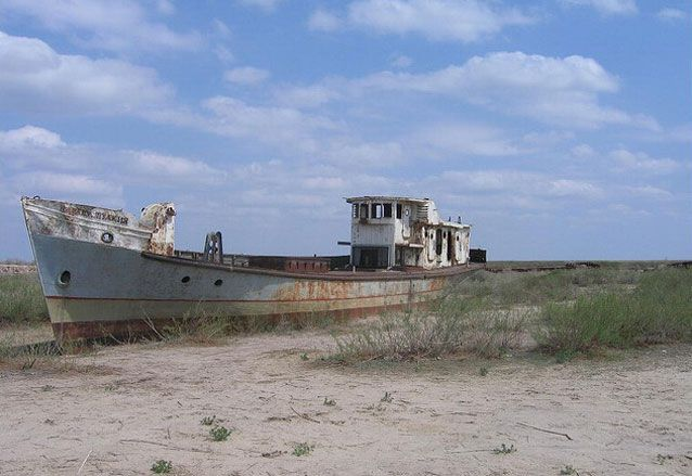Dry waterway with an old ship beached on the sand under a blue sky