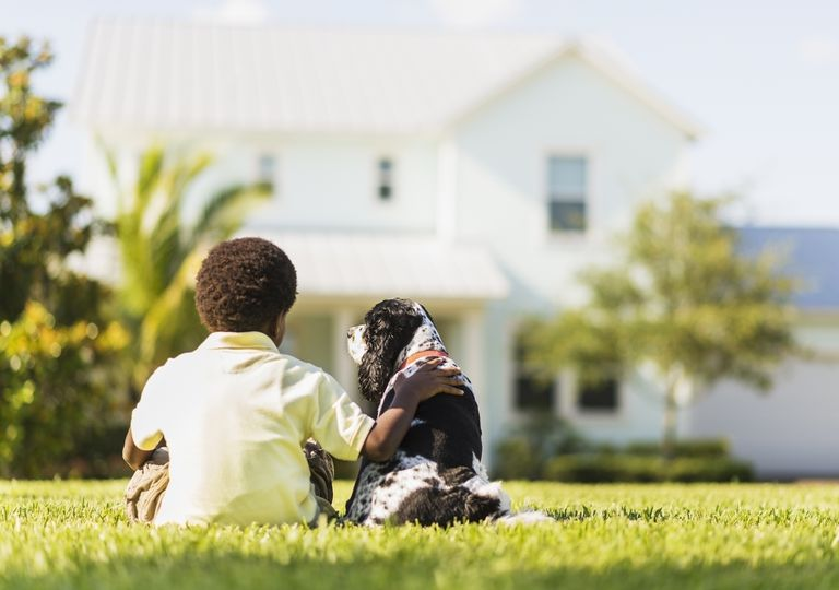 Back view of a boy and a dog sitting in front of a house