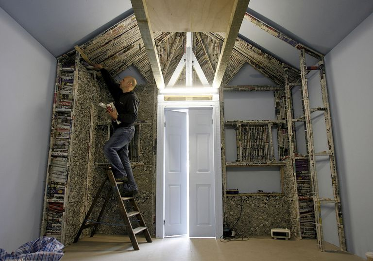 An artist standing on a ladder builds a house structure of our newspapers.