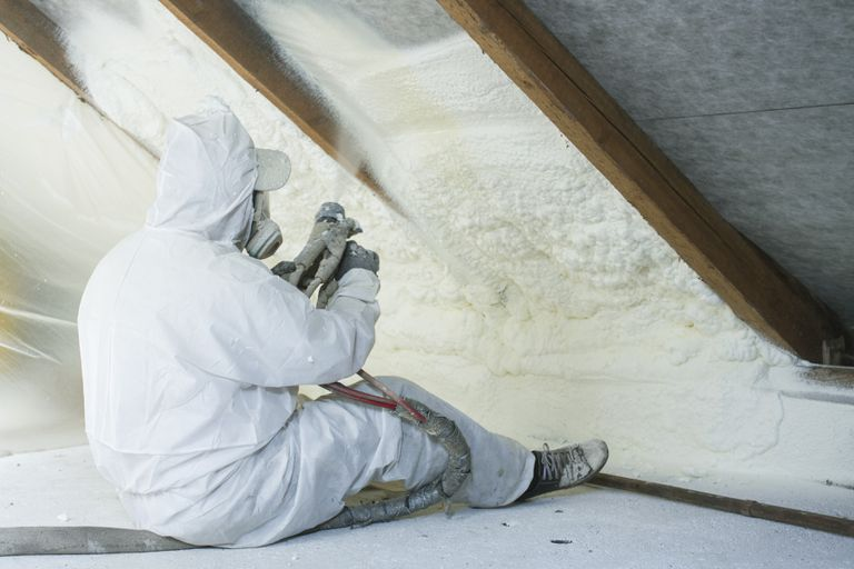 Person sitting on the floor in an attic space spraying foam insulation