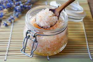 large glass lidded container filled with homemade salt scrub mixture with wooden spoon dipped in