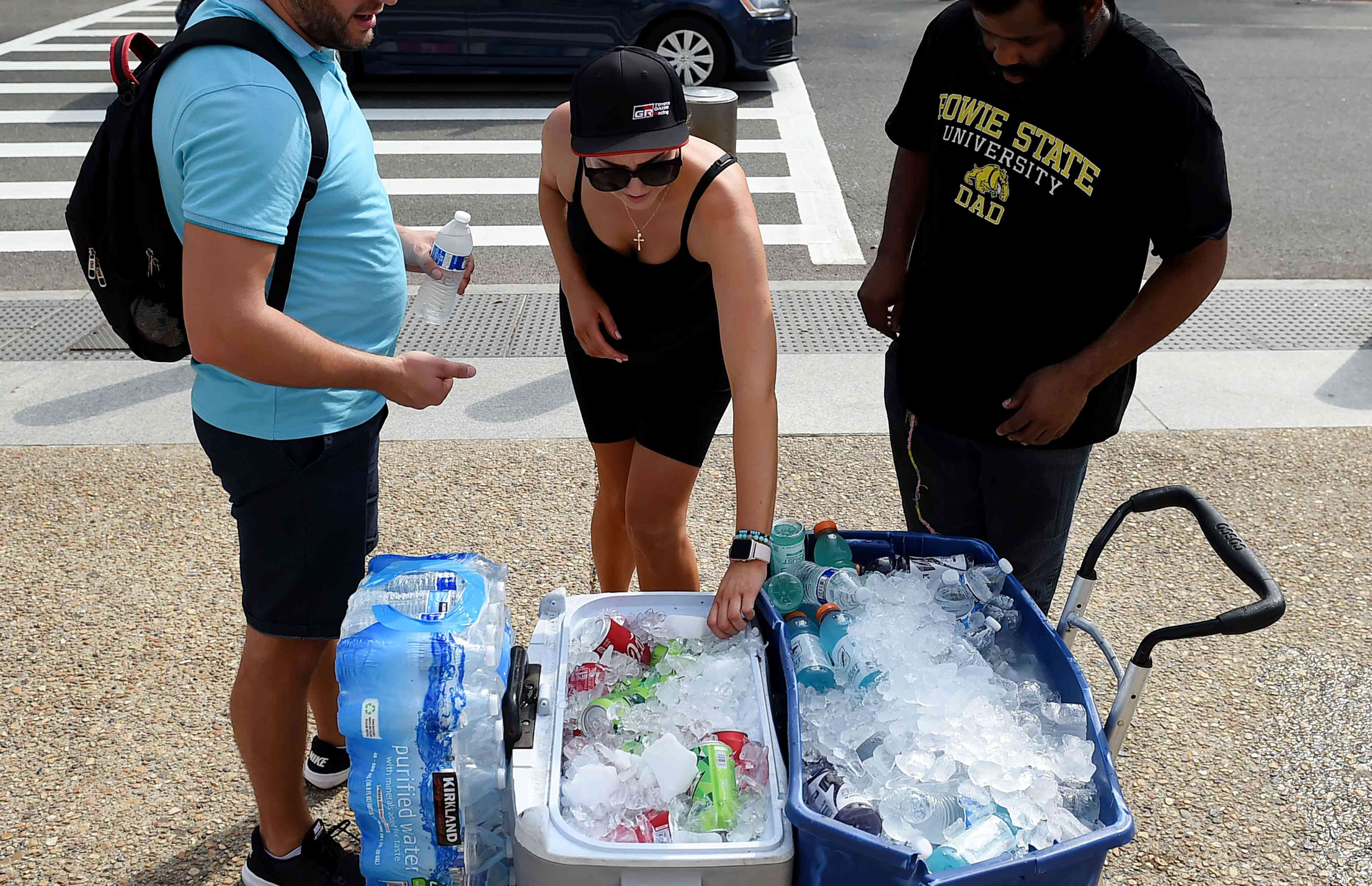 People getting cold drinks from a cooler