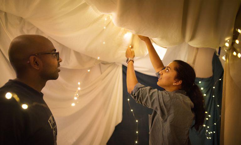 Couple building a blanket fort inside