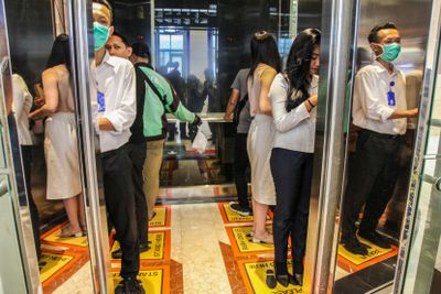 People socially distancing and wearing masks in an elevator
