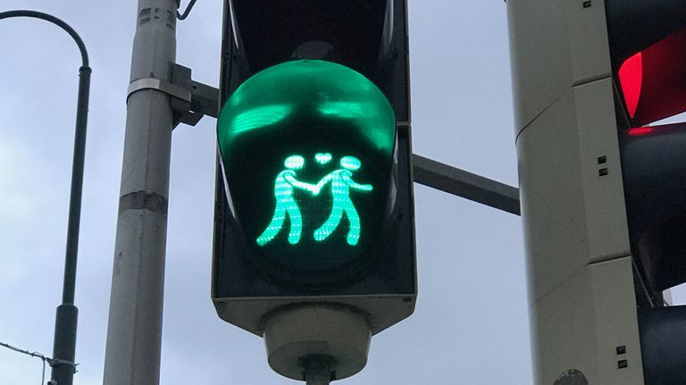 Crossing light in Vienna shows two people holding hands