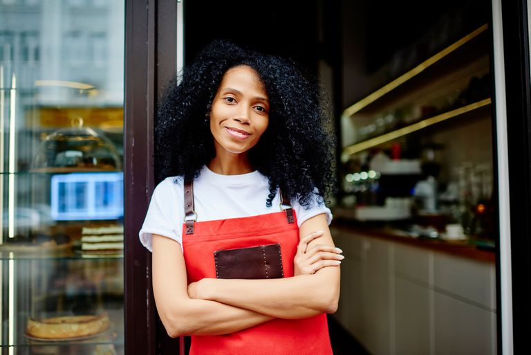 Busioness woman stands at door to her coffee shop