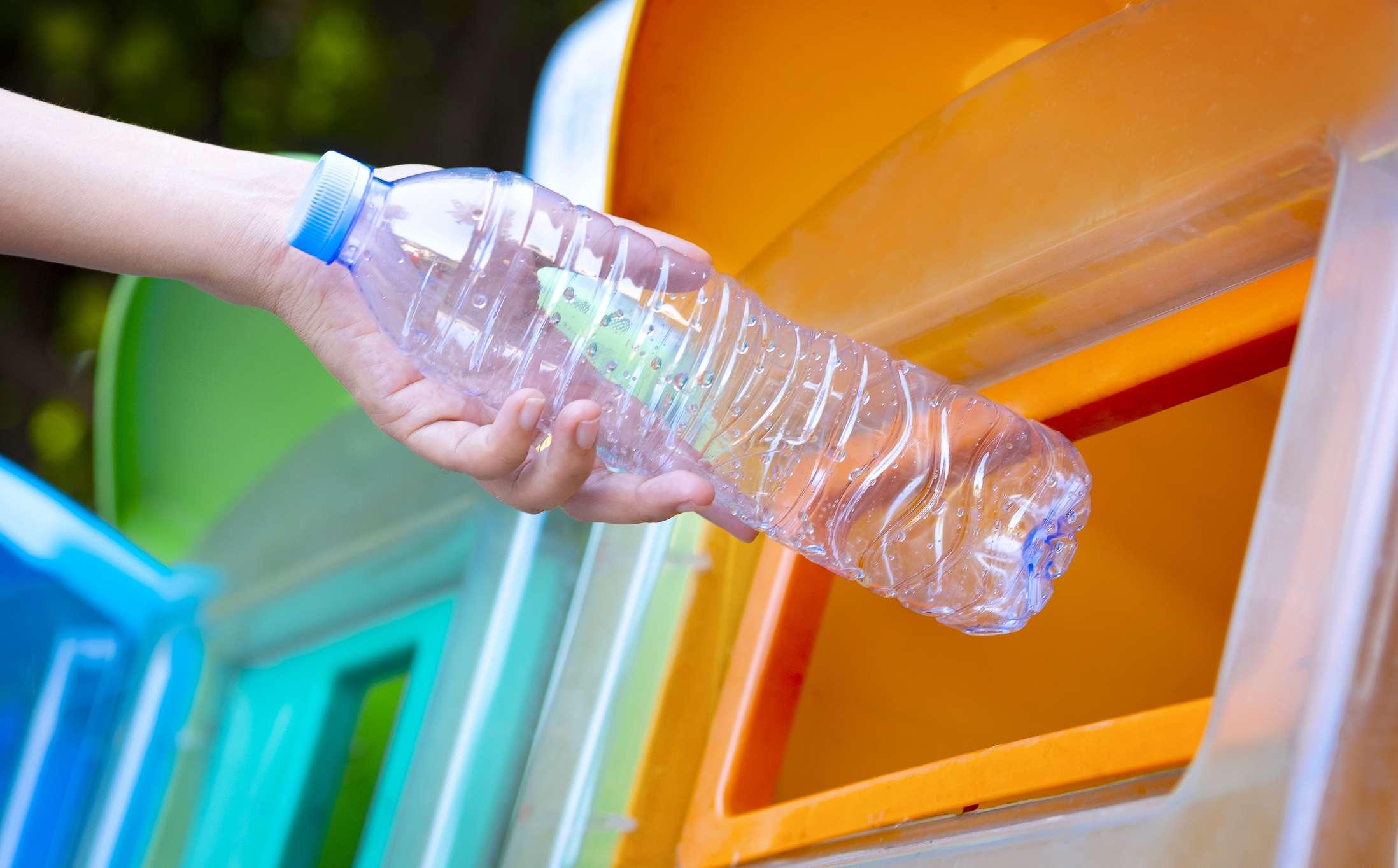 A hand puts a plastic bottle into a compost bin.