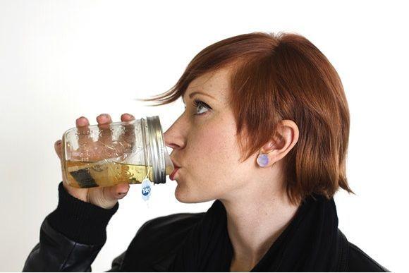 woman drinking tea from mason jar