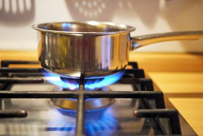 Silver pot over a blue gas flame on a stove