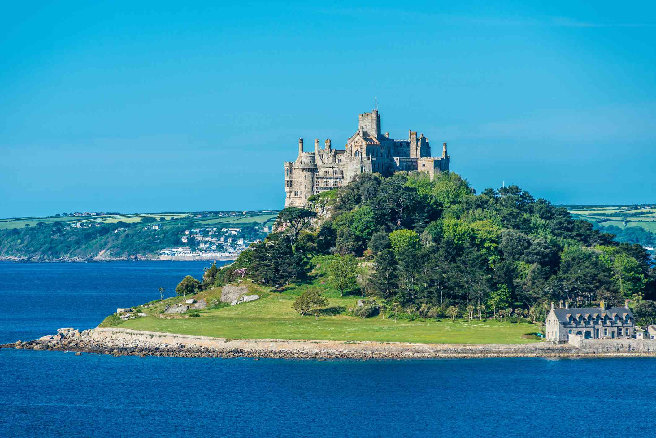 St. Michael's Mount, an elevated castle surrounded by lush green trees and water under a clear blue sky
