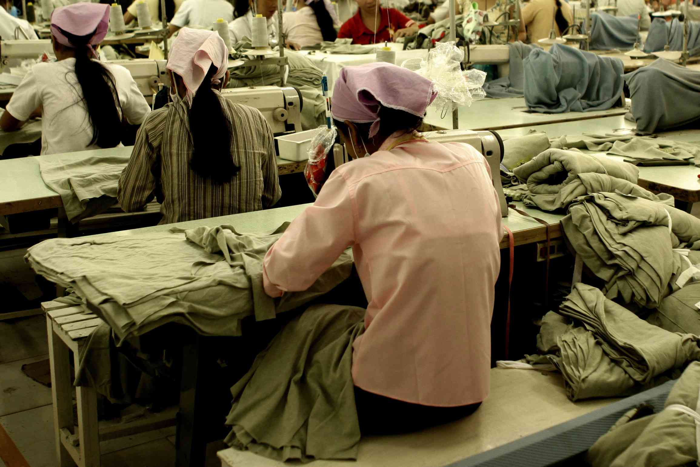 Workers sitting at sewing machines in a garment factory in Southeast Asia