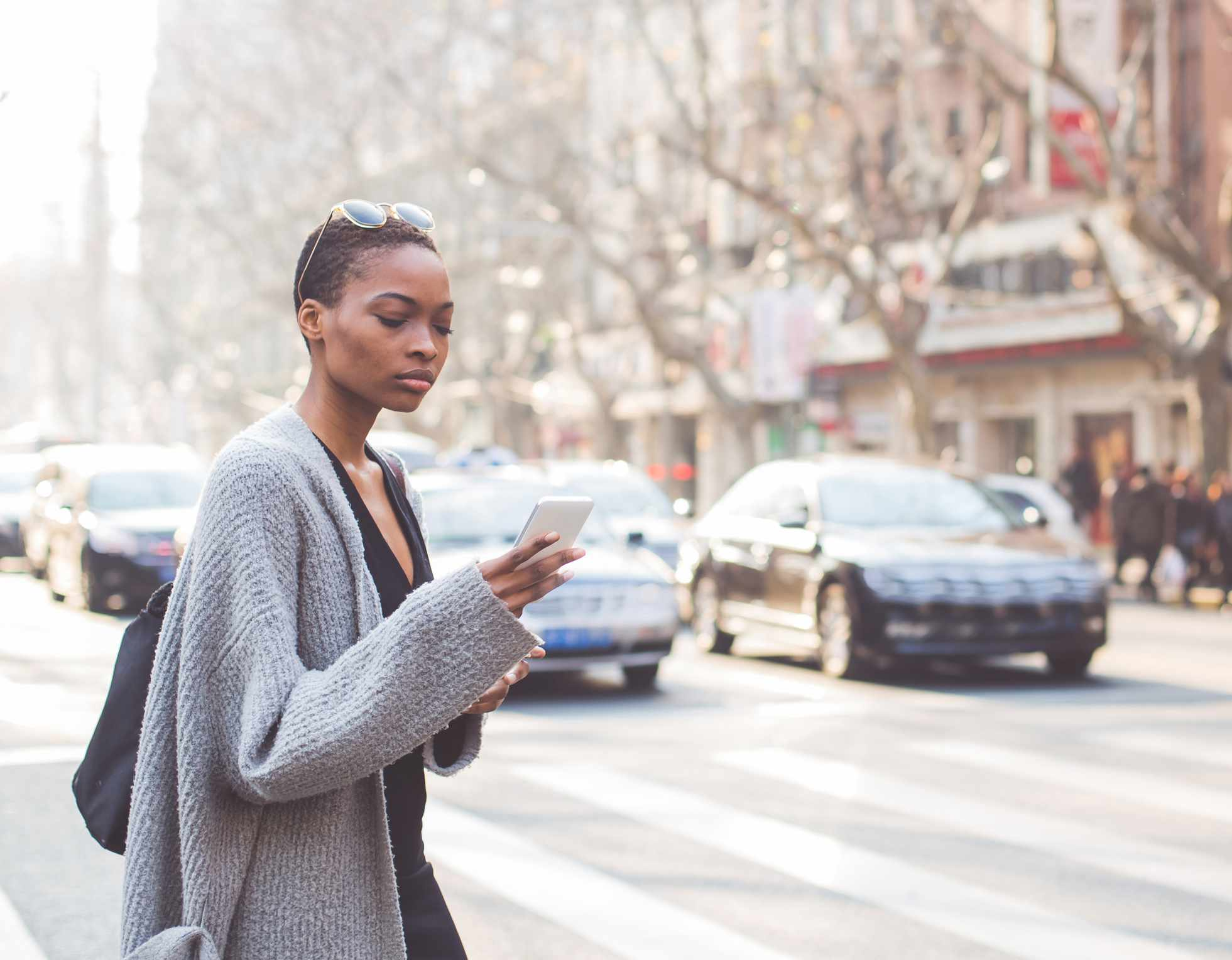 A young Black woman crosses the road looking at her phone.