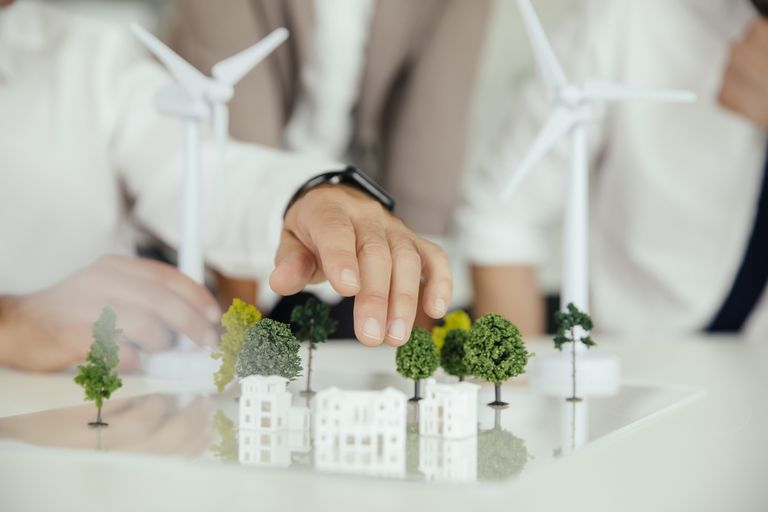 Hands touching miniature buildings in a sustainable setting surrounded by wind turbines.